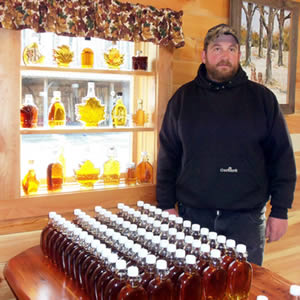 Inthewoods Sugar Bush owner with bottles of 100% Wisconsin maple syrup